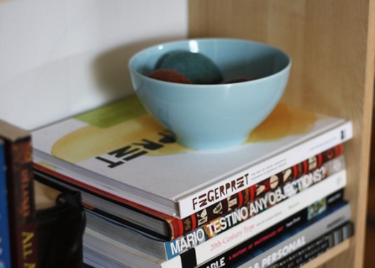 Placing an object or a bowl with some unique items on a stack of books lightens it up